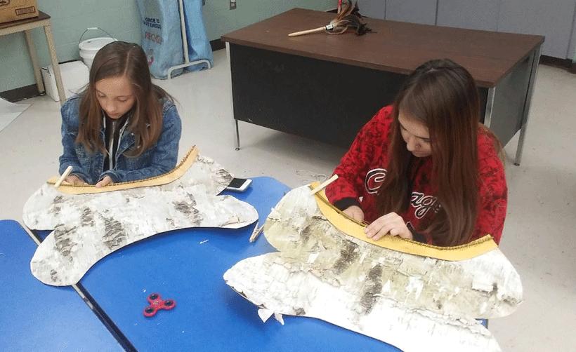 Two students work on birchbark canoes.
