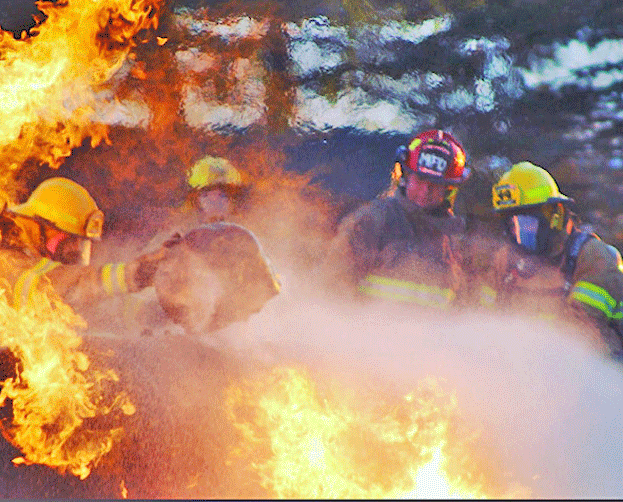 Firefighter Carlie Bray (left) shuts off the relief valve on a propane tank during hazmat training.