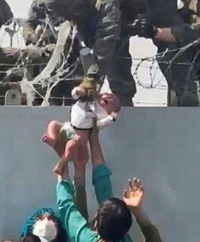An Afghan baby passed over a fence to an awaiting Marine.