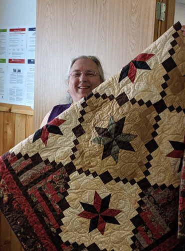 Faith in Action Director Theresa Eclov displays the grand prize in the 2019 Faith in Action Quilt Raffle.