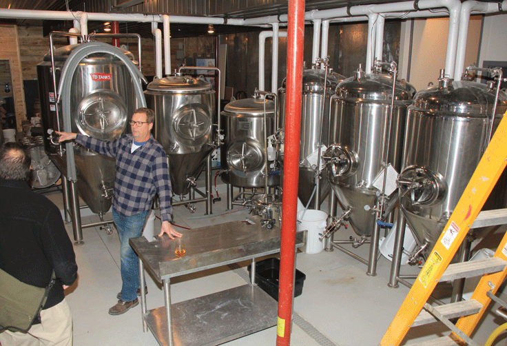 Portage Brewing Company co-founder and co-owner Mark Vondenkamp shows off the new brewery that now has twice as many beer barrels.