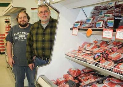 Mark Biessener, owner of Mark's Market (right), takes a break near the meat counter with his nephew, Michael Murray, who works the night shift as a stocker.