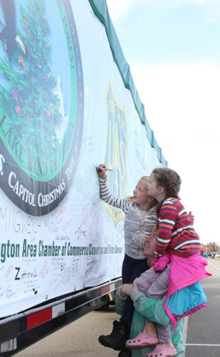 Sitting on their dad, Randall Morrison's shoulders, Aubrey and Avery write down a message that will be seen by thousands as the tree makes its way from Minnesota to Washington, D.C.