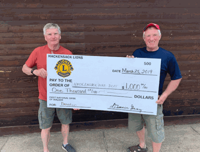 "Lion Jim Tuller (left) hands the ""big check"" to Chief Tony Peterson"