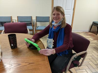 Faith in Action volunteer Jamie Wolske tests out the links on a new tablet for the Senior Connections Project.