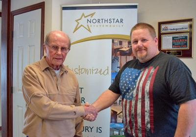 Ken Bresley (left) former owner of Village Homes, Walker, congratulates new owner Russ Rich.