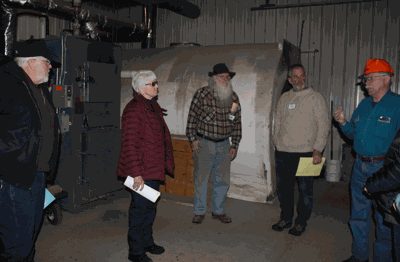 Norm Moody (right) explained how the wood gasification heating system works at Deep Portage Learning Center.