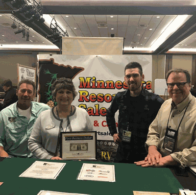 Leech Lake Chamber Executive Director Cindy Wannarka presents the First Business Dollar to (from left) Associate Broker Dan Houle of the Walker Area North office, Broker Mike Anderson and Sales Agent Ross Coyer.