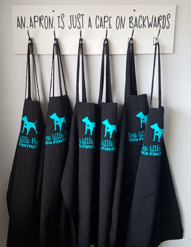 Half a dozen aprons hang ready for the next painting party at the One Little Piggy Signs studio or in a customer's home.