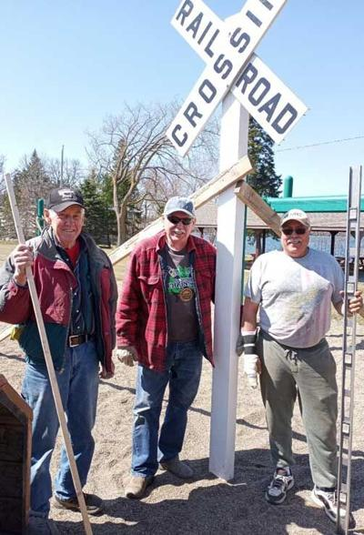 Hackensack Lions (from left) Lewie Schrupp, Rodney Damm, Joe DeJaeghere and Julie Cline (photographer) recently installed a new railroad crossing sign.
