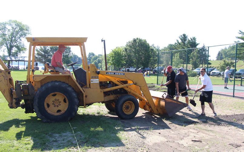 Dave Cochran (in the loader) and other pickle ball enthusiasts spread black dirt around the new courts before applying grass seed. Cochran paid for the entire project.