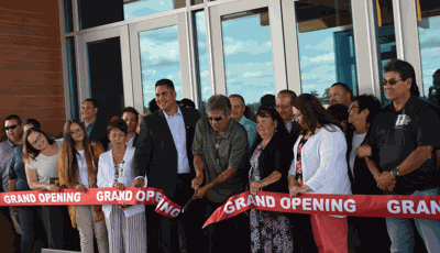 Wielding an oversized scissors, Leech Lake Tribal Chair Faron Jackson (center) cuts the ribbon for the grand opening of Cedar Lakes Casino and Hotel. Joining him are (front row to his left) Joe Jackson, Ass't. GM, Northern Lights; Stephanie Tanner; Amy Stangel; Breanna Miettinen, controller, Leech Lake Gaming; Heidi Bilyeu; Leroy Fairbanks, Dist. III Rep; (front row to Faron's right) Laurel Jackson, Faron's wife; Robbie Howe, Dist. I Rep; Audrey Emineth, GM, Cedar Lakes Casino; and Donnie Headbird. In the back row (left to right) are Derek Jackson, GM, White Oak Casino; Damien Thielke, Dir. of Investigations; Pete Paquette, Dir. of Human Resources; Mike Auger, Gaming Director; and Robbie Budreau, Jr., Executive Director of the Leech Lake Band of Ojibwe.