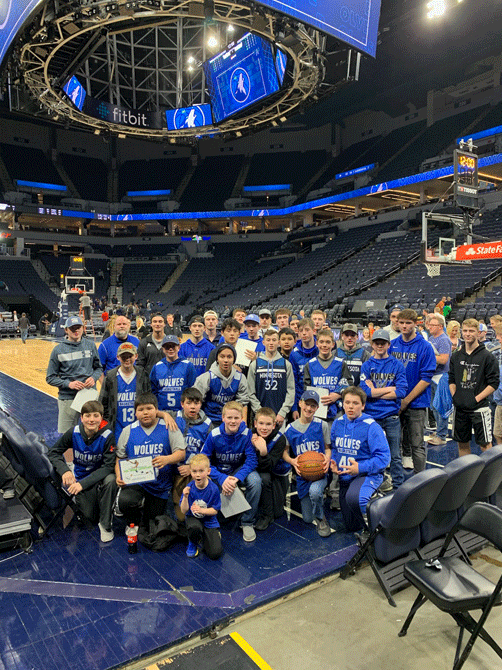 The WHA boys' basketball players pose for a photo on the floor of the Target Center.