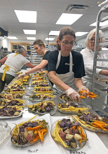 Erin and staff preparing a beef and potato vegetable platter for a wedding.