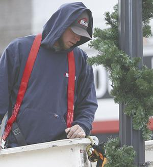 <p>Daniel Roberts, who's worked for the city for about three years, gets the greenery outside the Historic Walton County Courthouse just right Monday afternoon, Dec. 2, 2019. The 66th annual Monroe Christmas Parade will be Thursday night, bringing thousands of people to downtown.</p>