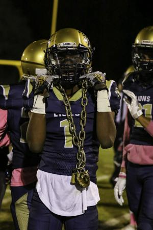 "<p>Jamal Price celebrates his first half interception against Notre Dame Academy last night with the team's ""turnover chain"". It was one of the five turnovers the defense forced in the Lions' 54-0 victory.</p>"