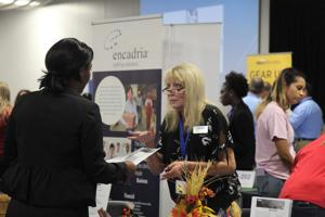 <p>An applicant speaks with representatives from Encadria staffing services.</p>