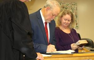 <p>Mayor David Keener signs the oath of office in Social Circle, Ga., on Monday night, Jan. 13, 2020, while Probate Judge Bruce Wright and PennyKeener look on at the city's Community Room.</p>