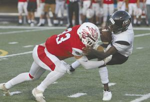 <p>Redskins' senior strong safety Ethan Ryan (33) delivers a big hit on the Stone Mountain quarterback during first quarter action Friday night.</p>