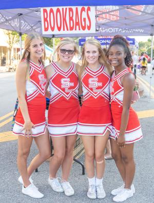 <p>Social Circle cheerleaders man the backpack booth at the Back to School Bash on Thursday, July 25, 2019, in downtown Social Circle, Ga.</p>