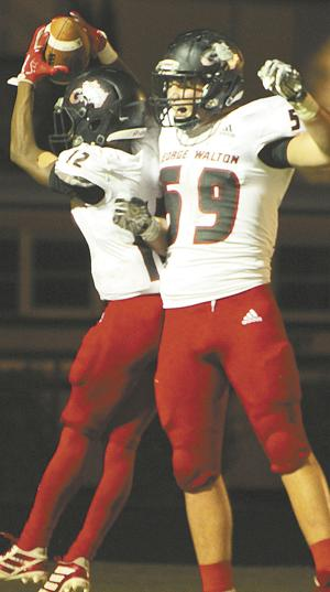 <p>Bryson Williams (12) and Austin Cole (59) celebrate a touchdown in George Walton Academy's 49-13 rout of Athens Christian on Friday night.</p>