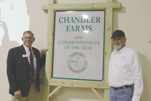 <p>From left, Dan Bennett, chairman of the board of supervisors for the Walton County Soil and Water Conservation District, presents the Conservationist of the Year award to Steve Chandler, owner of Chandler Farms in Good Hope.</p>