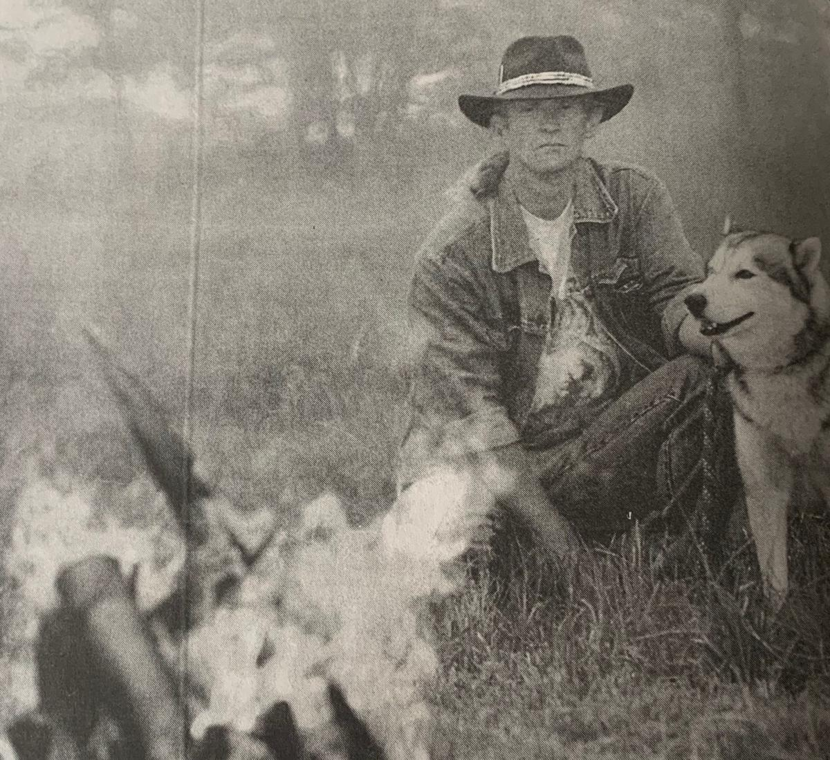 Steve Clark, wolf breeder, and his pet wolf, Timber, stare into a fire while camping in cool mountain temperatures in 1999.