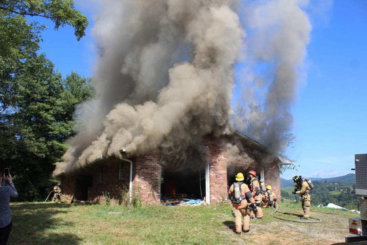 Smoke billows out of the brick house used for the firefighter training exercise on Aug. 17.