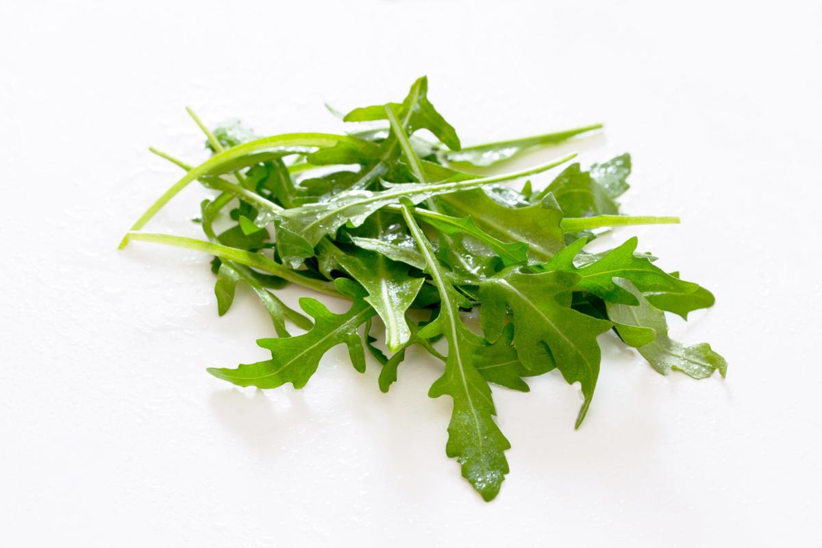 Arugula leaves on white background, selective focus.