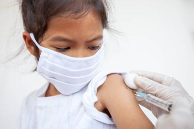 Patient wearing mask getting a shot