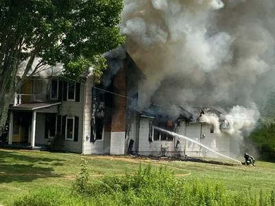 Fire fighters work to get a house fire under control on U.S. 421 on July 30.