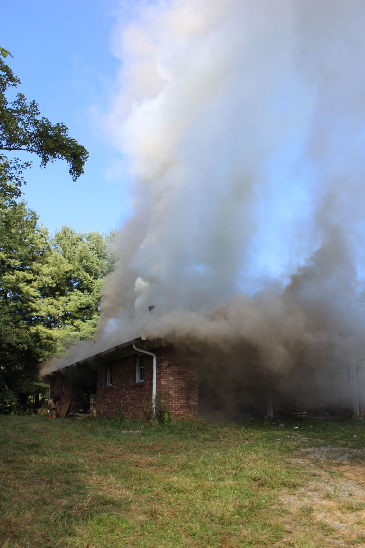 At a controlled burn and fire training on Aug. 17, smoke billows out of the house. Smoke carries harmful polycyclic aromatic hydrocarbons (PAHs) that increase the chance of cancer for firefighters.