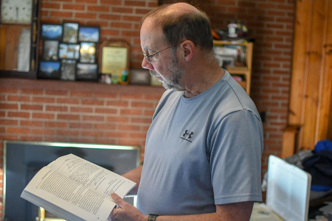 Steve Sudderth leafing through book