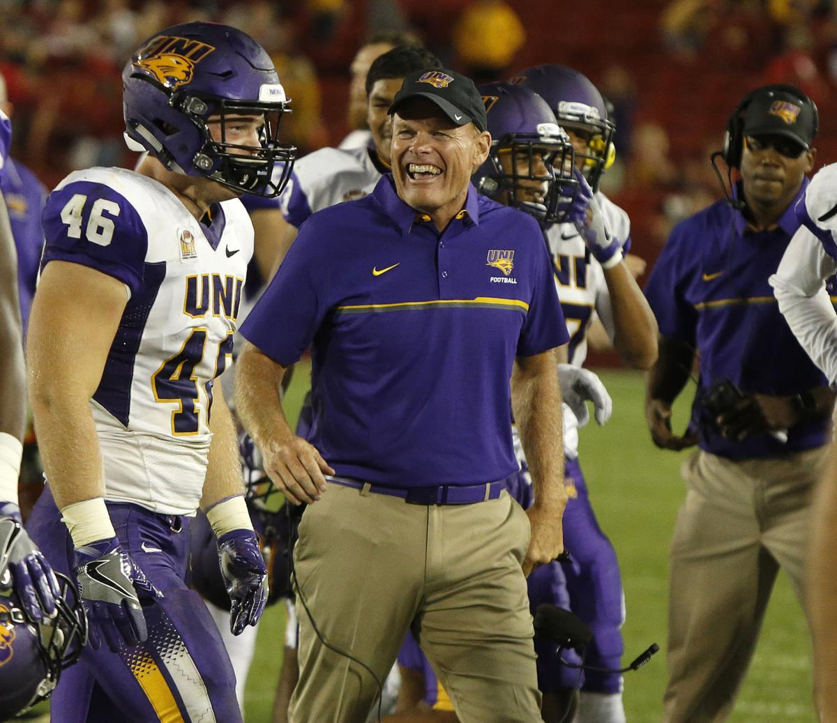 Northern Iowa head coach Mark Farley, center, congratulates his son Jared Farley, left, on his interception in the final seconds that sealed the Panthers' 25-20 win at Iowa State Saturday night. (Matthew Putney/Courier Photo Editor)
