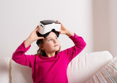 Girl wearing virtual reality goggles.