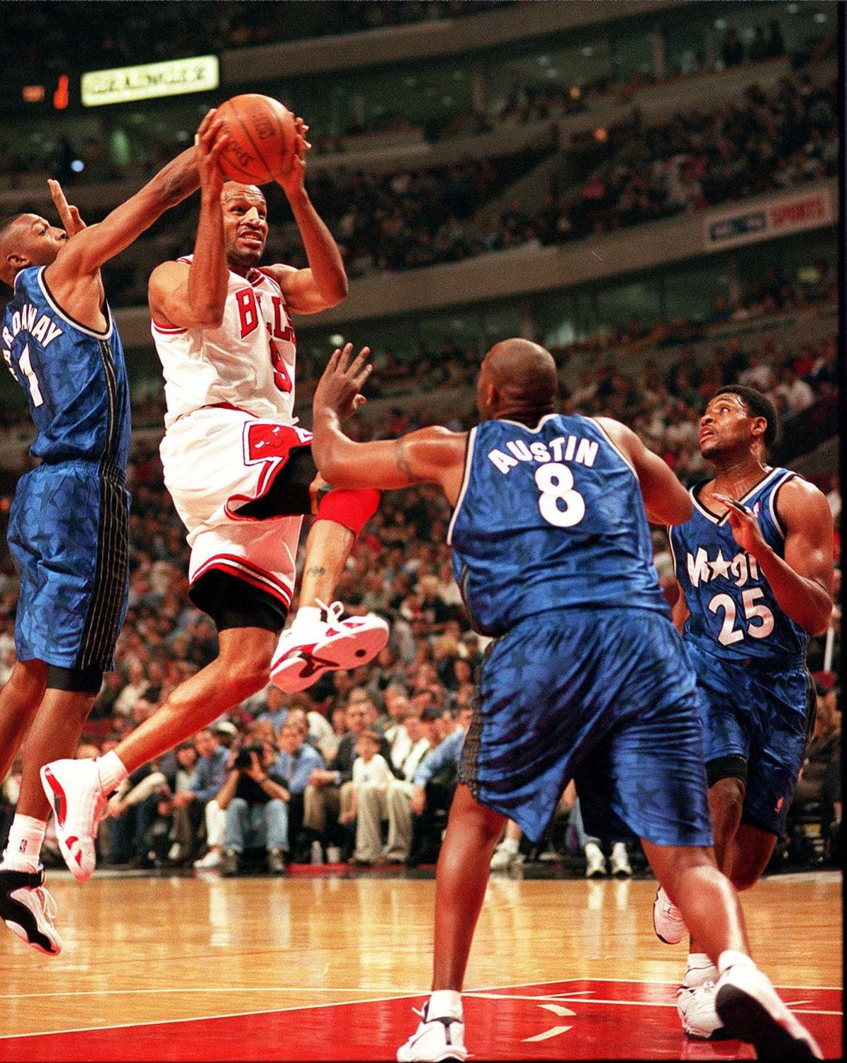 Bulls guard Ron Harper tries to shoot while surrounded by Magic players Anfernee Hardaway, left, Isaac Austin and Nick Anderson during a game at the United Center on May 5, 1999.