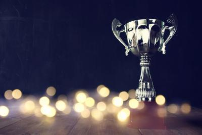 62414624 - low key image of trophy over wooden table and dark background, with abstract shiny lights