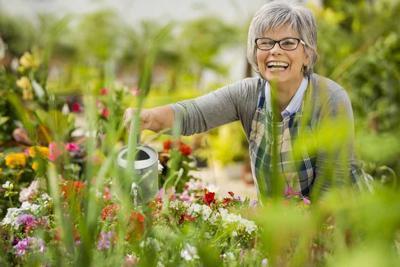 Elderly woman watering flowers