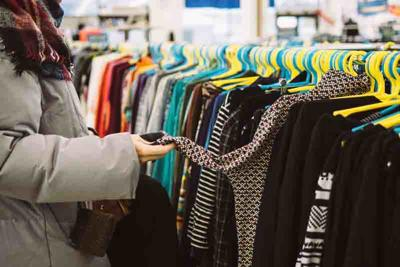 Young woman is browsing a rail of clothes at mall store