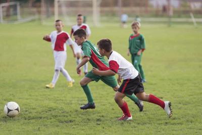22167896 - kids running with ball on football match
