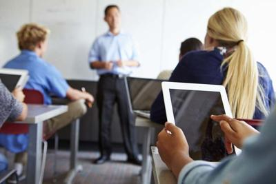 Close Up Of Pupil Using Digital Tablet In Classroom