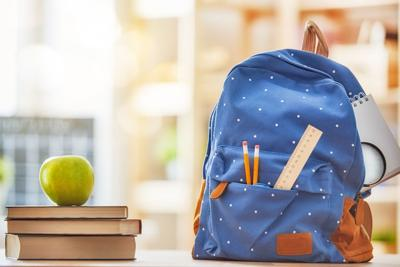 Apple, pile of books and backpack