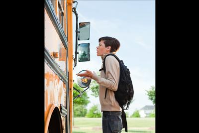Male high school student standing outside school bus door