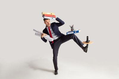 Young businessman in a suit juggling with office supplies in his office, isolated on white background