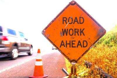Road work ahead sign with fast car