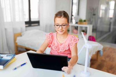 student girl using tablet computer at home