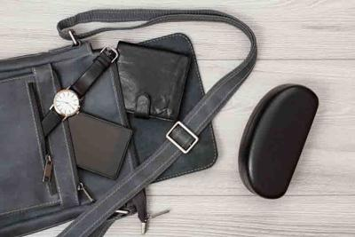 Leather shoulder bag for men with mobile phone, watch and wallet on it with gray wooden background