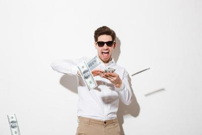 Portrait of a happy young man in sunglasses throwing