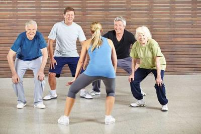Senior people dancing to music in gym