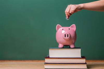 37509139 - person depositing money in a pink piggy bank on top of books with chalkboard in the background as concept image of the costs of education